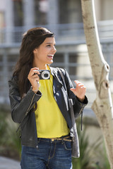 Woman holding a digital camera and smiling