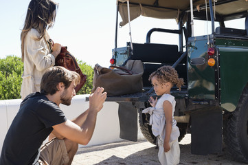 Man taking a picture of his daughter with a smartphone beside a SUV