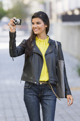 Woman taking a picture with a digital camera and smiling