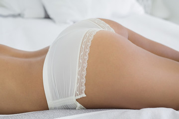 Mid section view of a woman lying on bed in lingerie