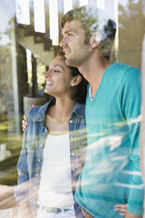 Smiling couple standing behind a glass wall