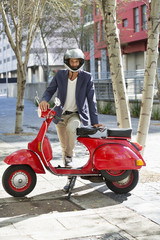 Portrait of a man standing with his scooter