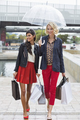 Female friends walking with shopping bags and smiling