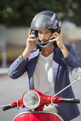 Man sitting on a scooter and wearing a helmet