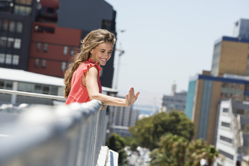 Smiling woman leaning against a railing and waving her hand