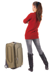 Back view of traveling brunette woman in jeans with suitcase loo