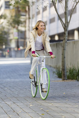Woman riding a bicycle on a street and smiling