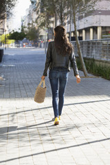Rear view of a woman walking with a handbag
