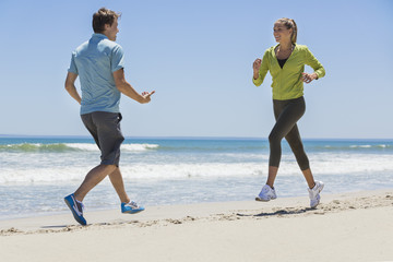 Woman jogging on the beach with her coach