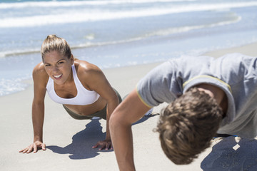 Woman exercising on the beach with her coach