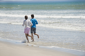 Two men running on the beach