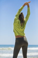 Rear view of a woman exercising on the beach
