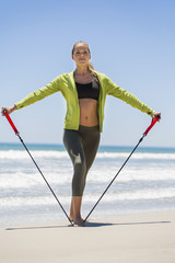 Woman exercising with a chest expander on the beach