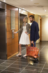 Couple standing outside an elevator at an airport