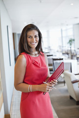 Portrait of a waitress holding a file in a restaurant