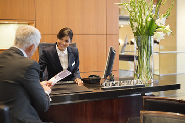 Businessman talking with a receptionist at the hotel reception counter