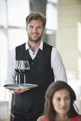 Woman sitting in a restaurant with a waiter holding a tray of wine glasses in the background
