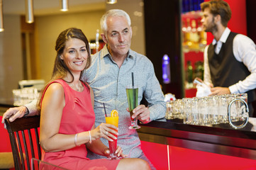 Couple enjoying drinks at the bar counter