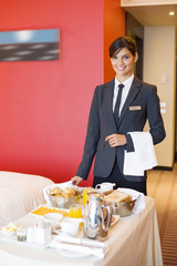 Portrait of waitress smiling with room service table in a hotel room