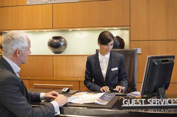 Receptionist working on a desktop pc with a businessman at the hotel reception counter