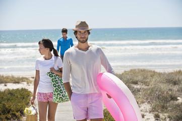 Friends walking on a boardwalk on the beach