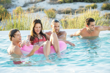 Group of friends enjoying in a swimming pool on the beach