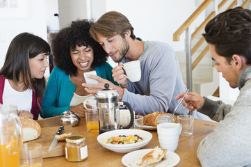 Friends sitting at a dining table and looking at a mobile phone