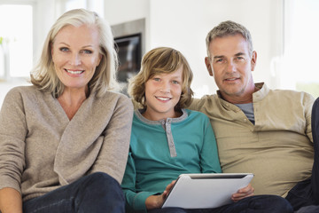 Portrait of a boy holding a digital tablet sitting with his grandparents