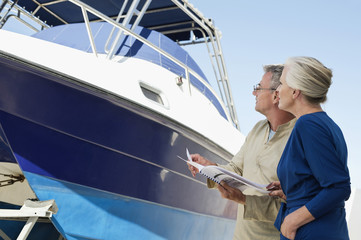 Couple standing near a yacht with a brochure