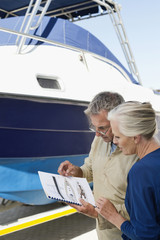 Couple reading a brochure near a yacht