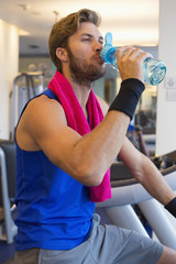 Man drinking water from a bottle in a gym