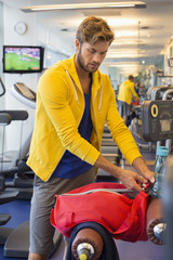 Man packing his bag in a gym after workout