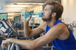Man drinking water from a bottle at a gym