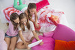 Three girls using a digital tablet at a slumber party