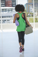 Rear view of a woman carrying an exercise mat and a bag