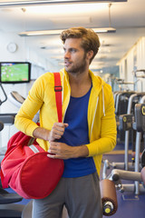 Man carrying a bag in a gym