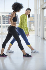 Woman exercising with her instructor in a gym