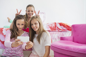 Three girls taking a picture of themselves with a mobile phone at a slumber party