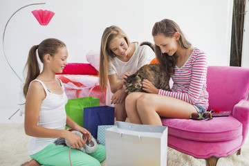 Girls playing with cat at a slumber party