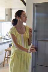 Woman opening a refrigerator in the kitchen