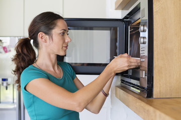 Woman putting food into an oven