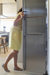 Woman looking into a refrigerator in the kitchen