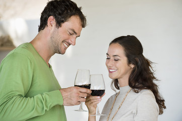 Couple toasting with wine glasses and smiling