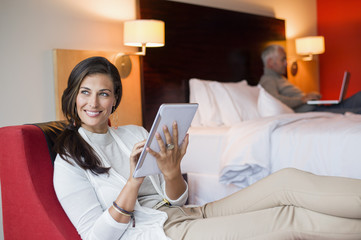 Woman using a digital tablet in a hotel room with her husband using laptop in the background