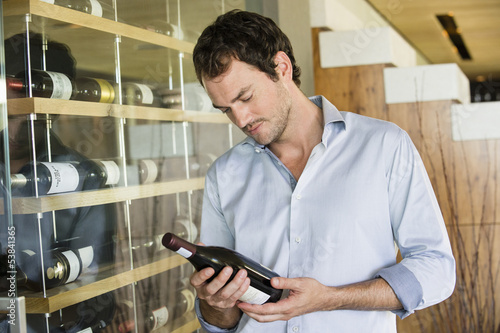 Man looking at a wine bottle