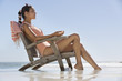 Beautiful woman sitting on a chair on the beach