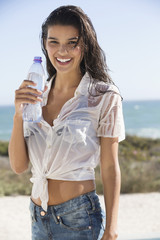 Beautiful woman holding a water bottle on the beach