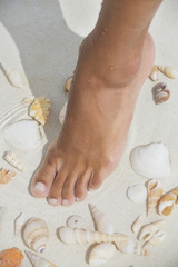 Woman's foot in water with seashell on the beach