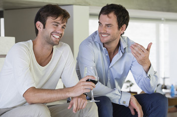 Smiling male friends with red wine