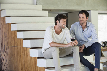 Smiling male friends sitting on steps with red wine